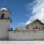 En una esquina hay un macizo campanario incorporado al muro frontal.